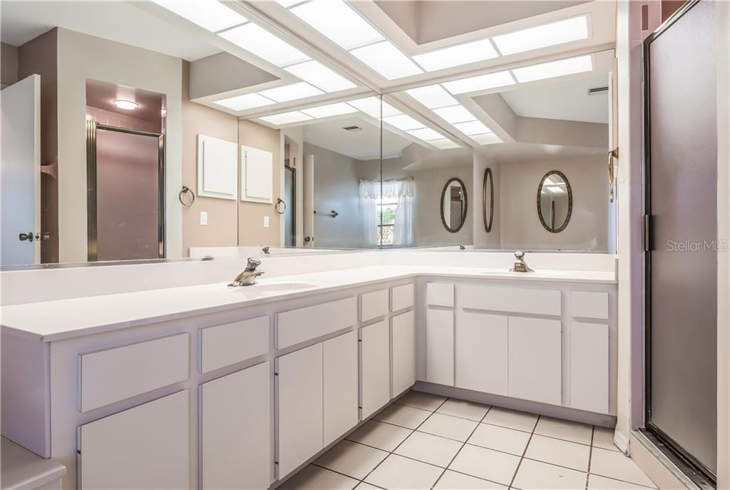 Master bathroom with dual sinks and walk in shower. - Single Family Home for sale at 11010 Deerwood Ave, Englewood, FL 34224 - MLS Number is D5921766
