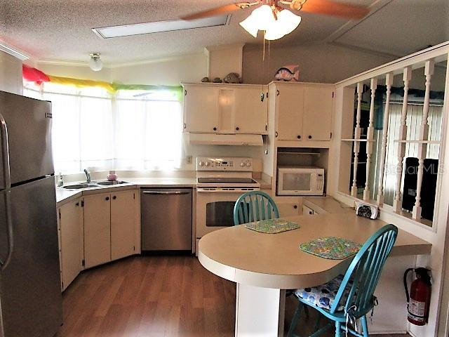 Kitchen has wood laminate flooring, ample cabinetry, ceiling fan and a breakfast bar - Manufactured Home for sale at 1800 Englewood Rd #95, Englewood, FL 34223 - MLS Number is D6103776