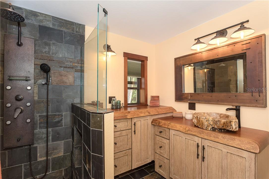 Master Bath features custom mahogany top vanities with petrified wood sink - Single Family Home for sale at 1199 Seahorse Ln, Englewood, FL 34224 - MLS Number is D6110877