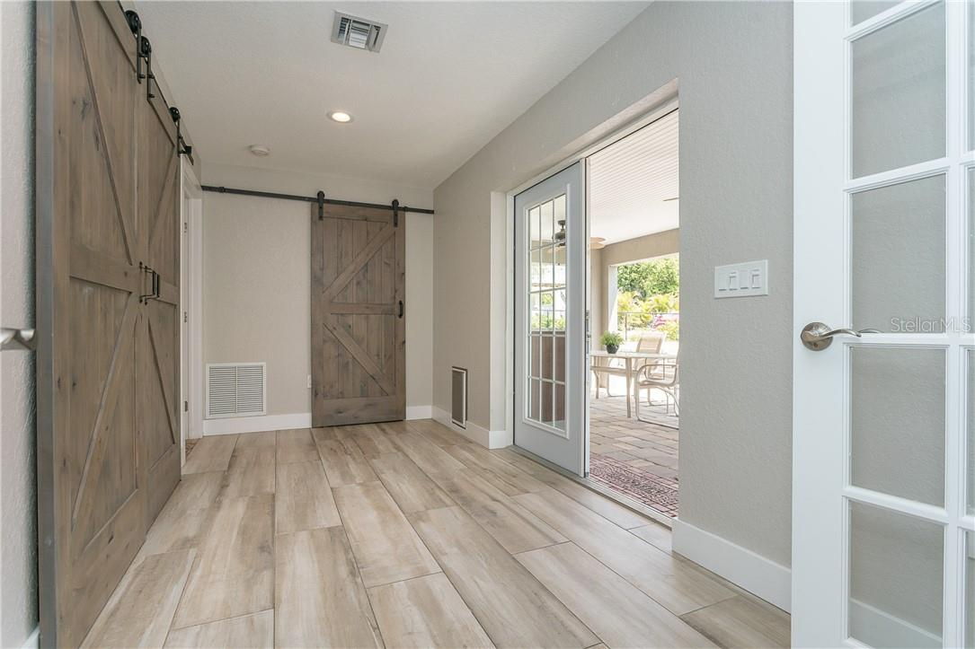 French Doors to the outside kitchen/dining area and absolutely fantastic flooring and upgraded sliding barn doors,  This is also grand entrance to master ensuite - Single Family Home for sale at 1661 New Point Comfort Rd, Englewood, FL 34223 - MLS Number is D6117712