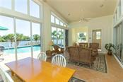 This view of the lanai shows a half-bath and a sitting or plant nook on the far end. - Single Family Home for sale at 1439 Deer Creek Dr, Englewood, FL 34223 - MLS Number is D5921060