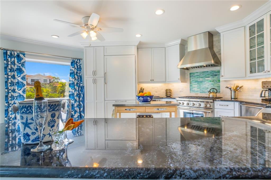 Beautiful blue granite countertops are complemented by tumbled Carrera marble and hand-poured glass tile. - Single Family Home for sale at 511 Loquat Dr, Anna Maria, FL 34216 - MLS Number is T3196169