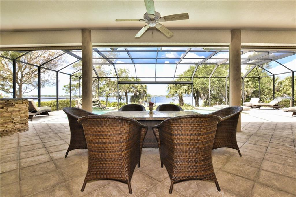 Additional spacious and comfortable seating in the shade, if you desire, featuring a fire-pit table. - Single Family Home for sale at 2839 Mill Creek Rd, Port Charlotte, FL 33953 - MLS Number is C7238545