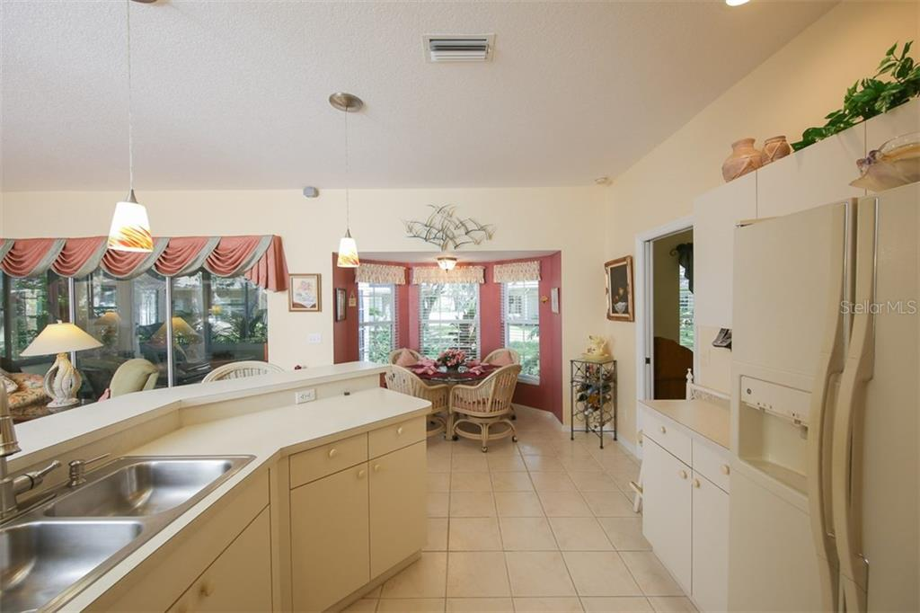 Kitchen looking into the kitchen nook that overlooks the beautiful outdoors - Villa for sale at 1234 Green Oak Trl, Port Charlotte, FL 33948 - MLS Number is C7243720