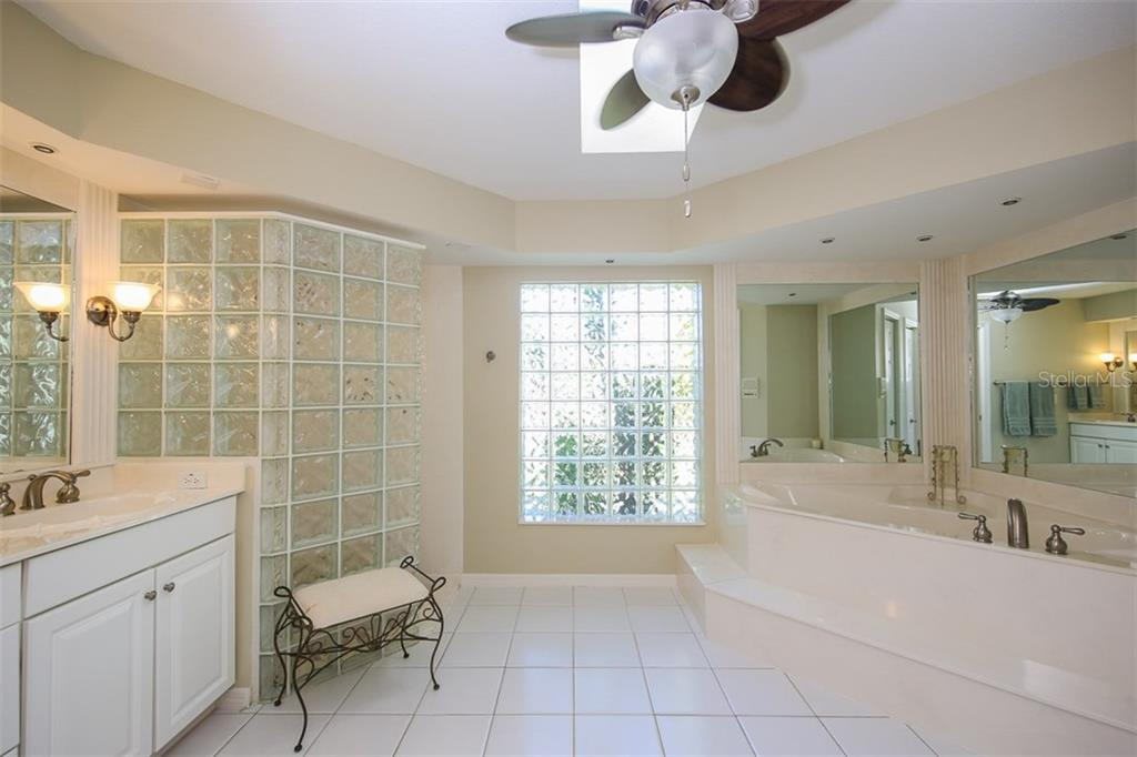 Master bathroom has a dual sink vanity, walk-in shower, and large soaking tub - Single Family Home for sale at 4407 Albacore Cir, Port Charlotte, FL 33948 - MLS Number is C7245070