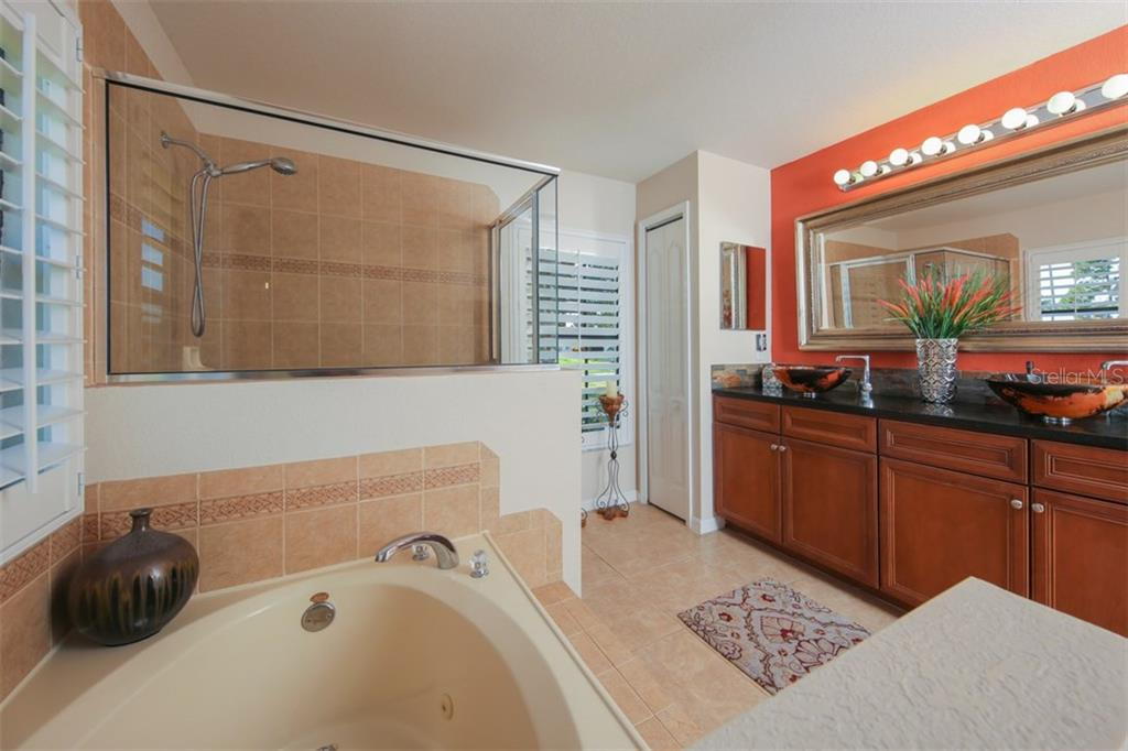 Remodeled master bathroom with dual pedestal sinks, wood cabinets and granite counters - Single Family Home for sale at 220 Broadmoor Ln, Rotonda West, FL 33947 - MLS Number is C7248036