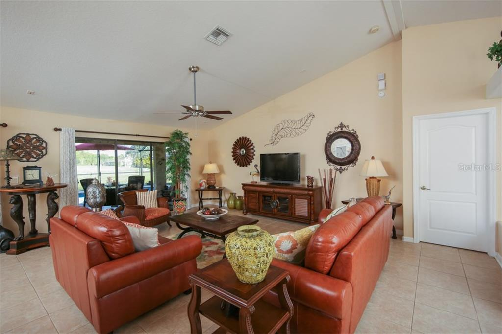 Charming great room opens to the stunning outdoor lanai and pool - Single Family Home for sale at 220 Broadmoor Ln, Rotonda West, FL 33947 - MLS Number is C7248036