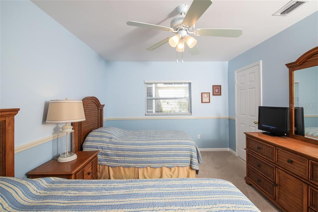 Bedroom 3 features walk-in closet. - Single Family Home for sale at 126 Bangsberg Rd Se, Port Charlotte, FL 33952 - MLS Number is C7409866