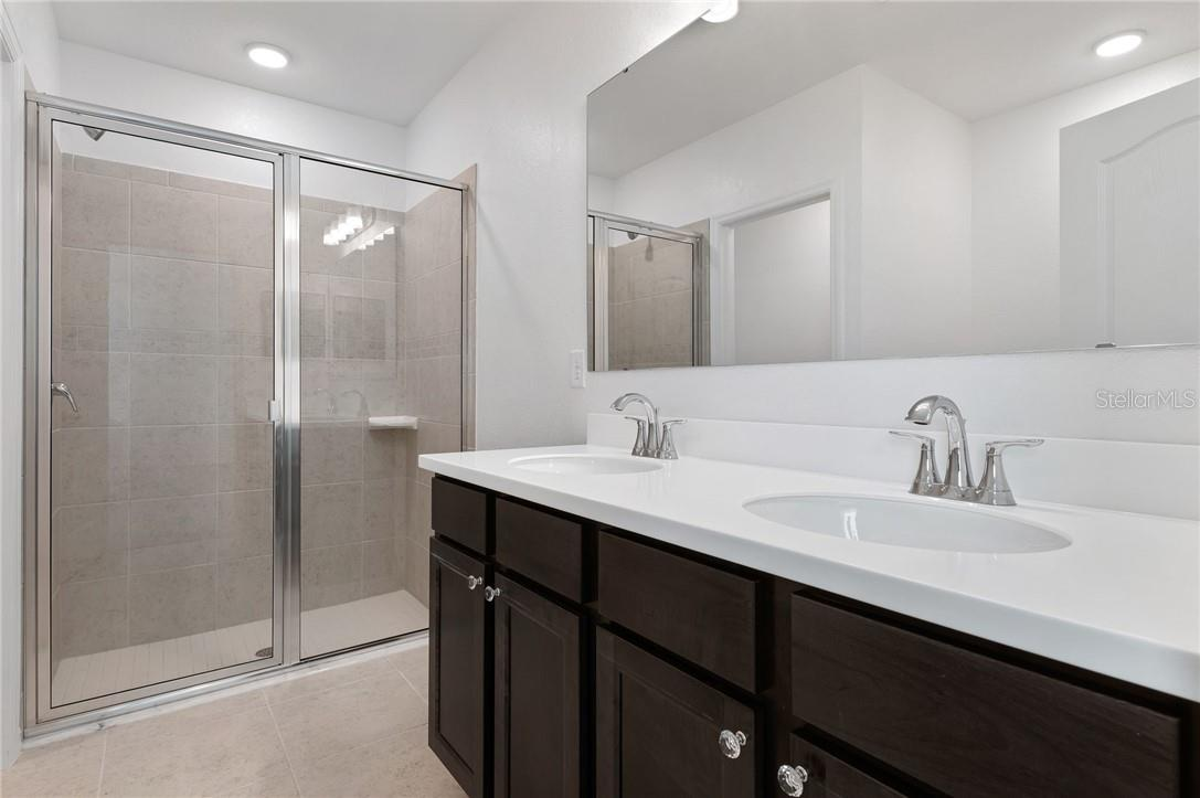 Dual sinks in the Master Bathroom and a view of the walk-in shower.  Out of view is the separate bath tub for the perfect soak after a long day. - Single Family Home for sale at 2082 Apian Way, Port Charlotte, FL 33953 - MLS Number is C7441465