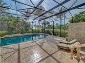 Gas fireplace and bank of french doors to lanai and pool - Single Family Home for sale at 6150 Manasota Key Rd, Englewood, FL 34223 - MLS Number is C7415176