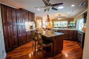 Breakfast island and ample storage in this well-equipped kitchen which overlooks the great room revealing canal and pool views. - Single Family Home for sale at 1440 Appian Dr, Punta Gorda, FL 33950 - MLS Number is C7425399