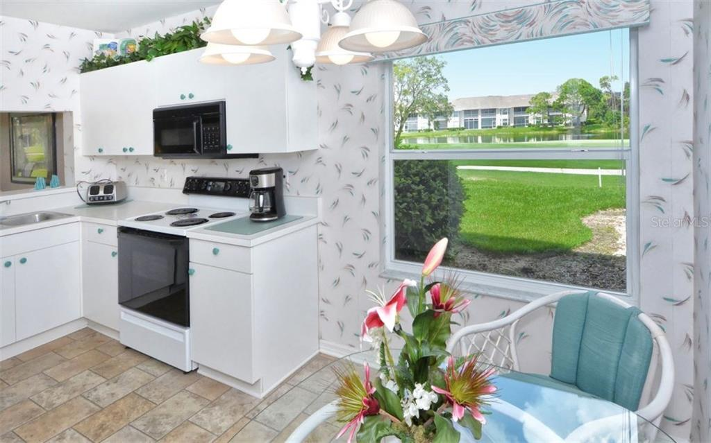 View of course and lake from kitchen dinette area. - Condo for sale at 9630 Club South Cir #6103, Sarasota, FL 34238 - MLS Number is A4166105