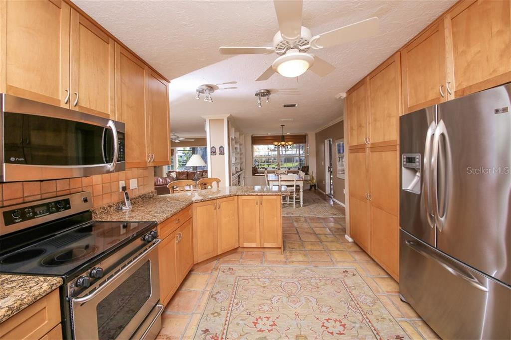 Renovated kitchen with tall wood cabinetry, stainless appliances, designer lighting, granite counter-tops, and more. - Single Family Home for sale at 5281 Cape Leyte Way, Sarasota, FL 34242 - MLS Number is A4171478