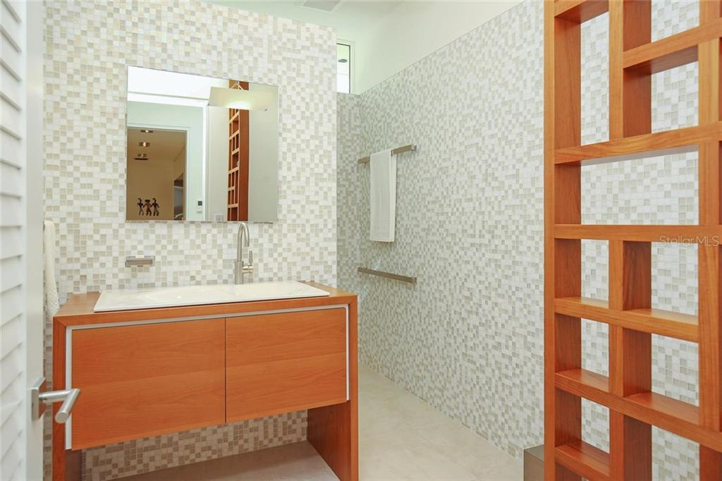 Downstairs full guest bathroom includes walk-in shower with rain head and teak cabinetry. - Single Family Home for sale at 593 Rountree Dr, Longboat Key, FL 34228 - MLS Number is A4172941