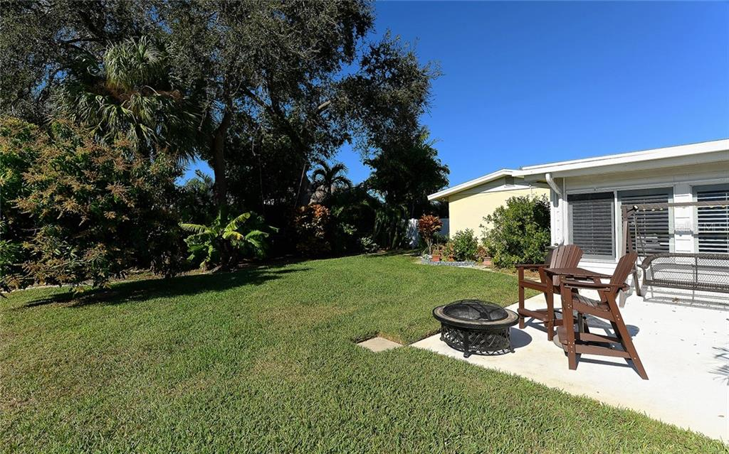 Rear Yard and  Open Patio with Mature Tropical Landscaping - West - Single Family Home for sale at 1532 Shelburne Ln, Sarasota, FL 34231 - MLS Number is A4173872