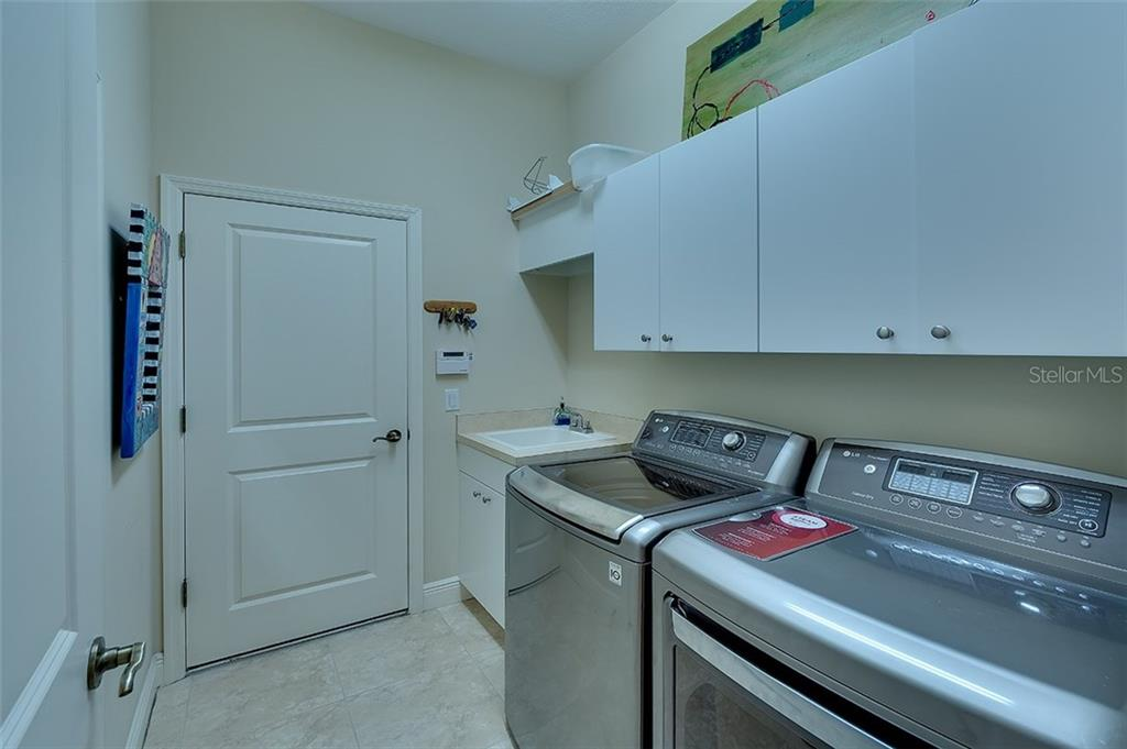 Utility room with sink and storage cabinets - Single Family Home for sale at 7254 Lake Forest Gln, Lakewood Ranch, FL 34202 - MLS Number is A4174107