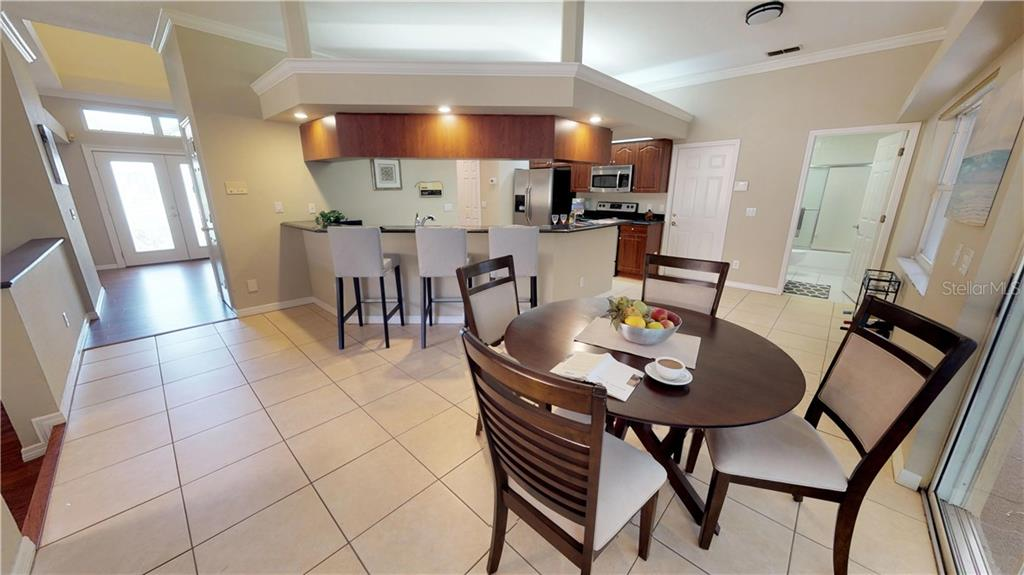 Another view of the casual eating area, the large wrap around bar, looking into the ground floor bathroom that has a door access to the pool as well. - Single Family Home for sale at 9122 16th Avenue Cir Nw, Bradenton, FL 34209 - MLS Number is A4189396