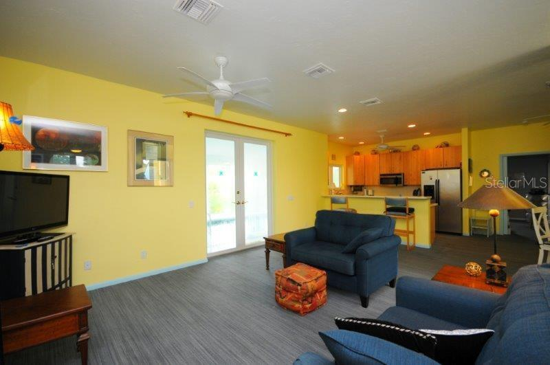 Living room /great room is open to the breakfast bar and kitchen. It also offers a view to the front through high glass doors and a view to the pool. - Single Family Home for sale at 3319 Mayflower St, Sarasota, FL 34231 - MLS Number is A4189488