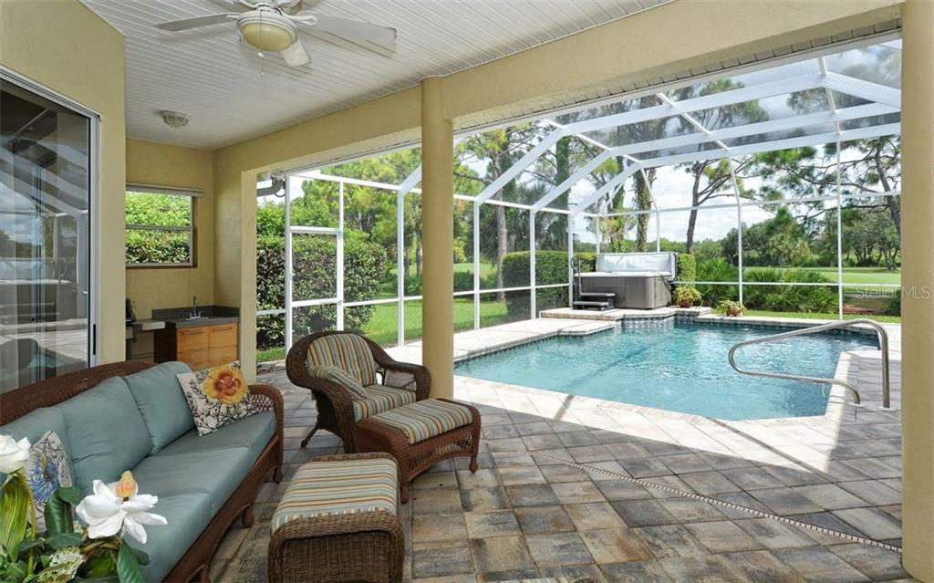 Lots of under roof space on this paver topped lanai.  The pool is heated and the hot tub awaits. There's an outdoor kitchen area and an outside shower (not pictured.) Sweeping private golf course views. - Single Family Home for sale at 8747 Grey Oaks Ave, Sarasota, FL 34238 - MLS Number is A4195019