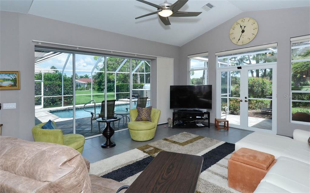 Family room has vaulted ceiling, oversized pocketing slider to the lanai, french doors to a comforting lanai seating area - Single Family Home for sale at 8747 Grey Oaks Ave, Sarasota, FL 34238 - MLS Number is A4195019