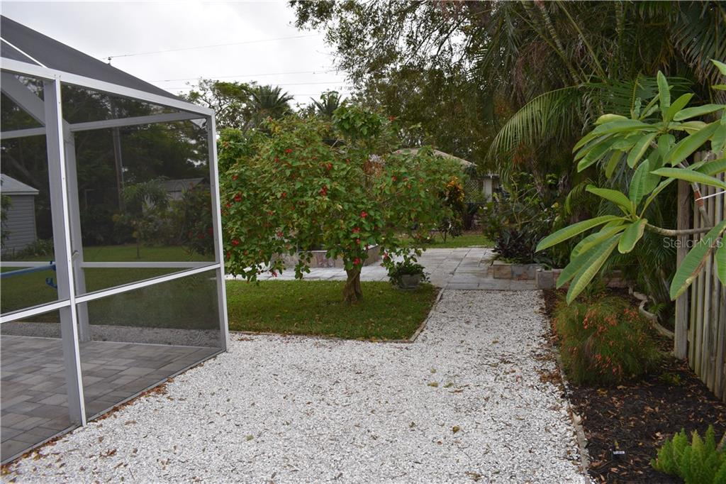 South side tasteful, maintenance easy shell walkway to the backyard patio. You will enjoy the lush, well kept, minimalist Florida landscaping. - Single Family Home for sale at 1133 Riviera St, Venice, FL 34285 - MLS Number is A4197682