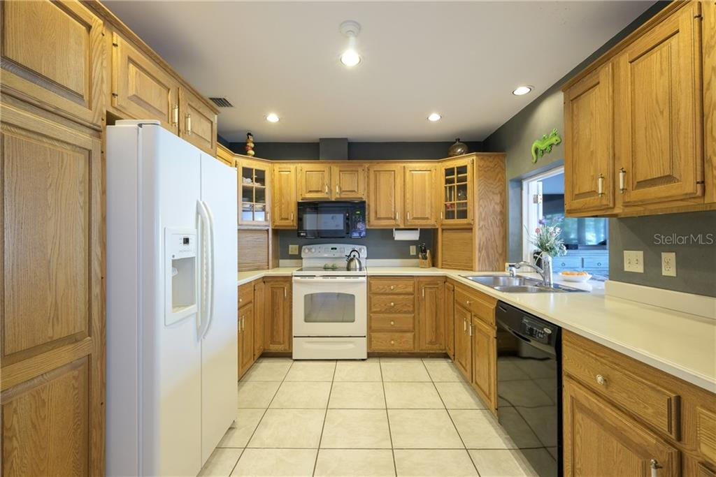 Kitchen with pass through to the family room, oak cabinets and Corian tops. - Single Family Home for sale at 5633 Cape Leyte Dr, Sarasota, FL 34242 - MLS Number is A4207008