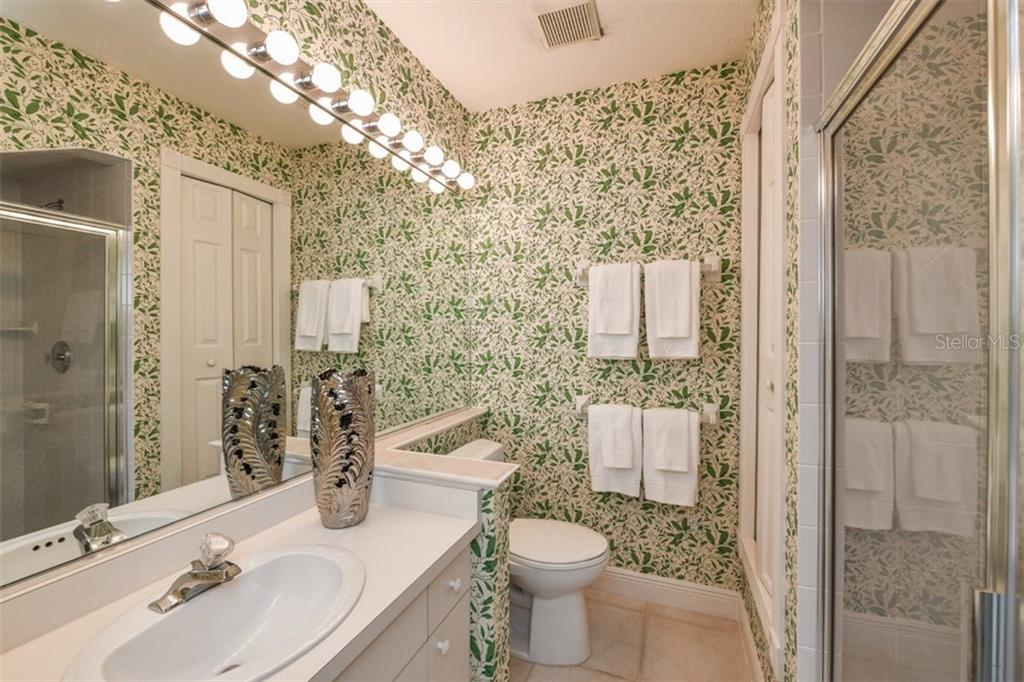 Full ensuite Bath #3 with nice glassed shower plus a linen closet. - Single Family Home for sale at 5585 Siesta Estates Ct, Sarasota, FL 34242 - MLS Number is A4211109