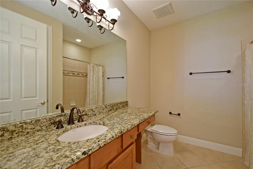 Guest Bath with Granite counters, Moen faucets, and wood cabinets. - Single Family Home for sale at 3729 Summerwind Cir, Bradenton, FL 34209 - MLS Number is A4215992
