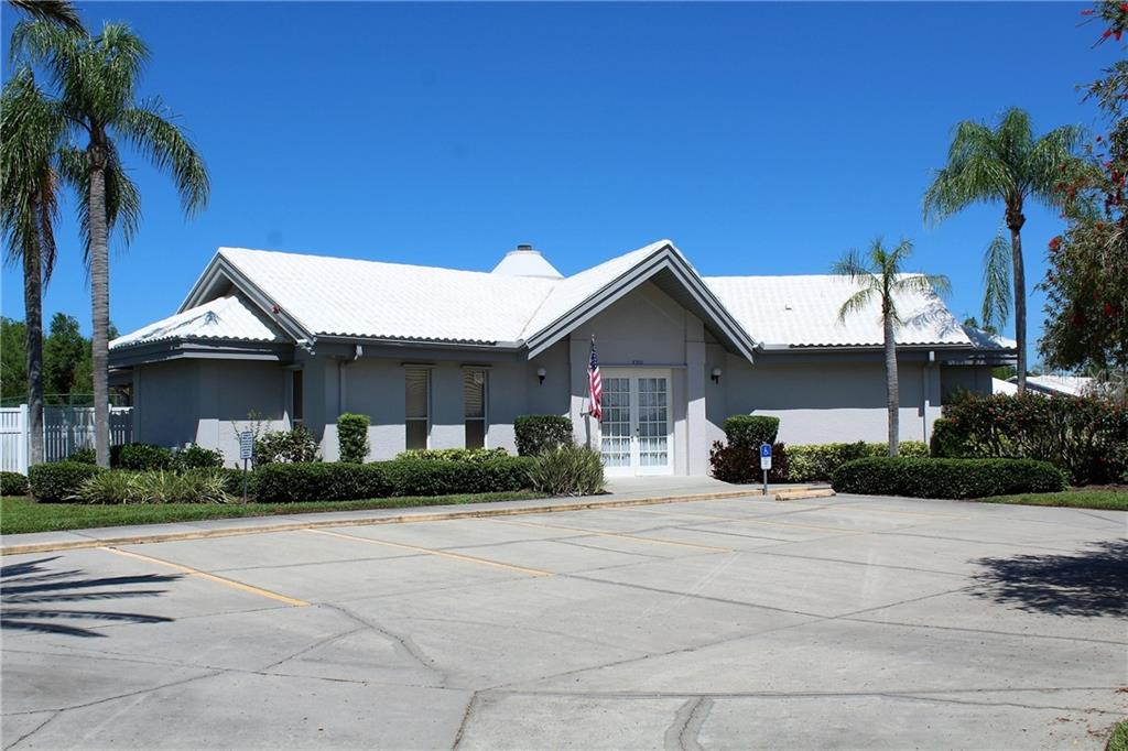 The clubhouse greets you as you enter the community. - Villa for sale at 5438 Kelly Dr #12, Sarasota, FL 34233 - MLS Number is A4400319