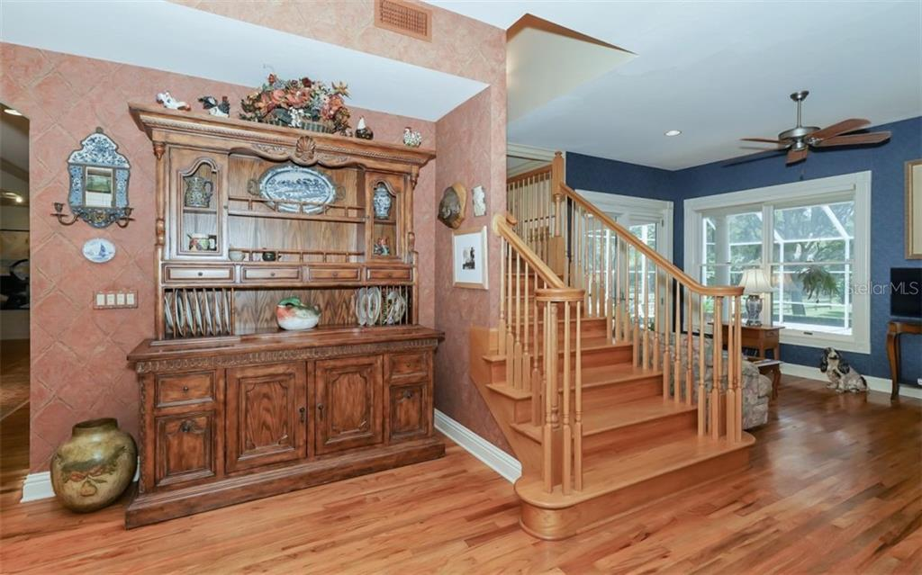 Beautiful wood stair case leading to the three large ensuite bedrooms upstairs, along with their own family room space. - Single Family Home for sale at 7866 Saddle Creek Trl, Sarasota, FL 34241 - MLS Number is A4407172