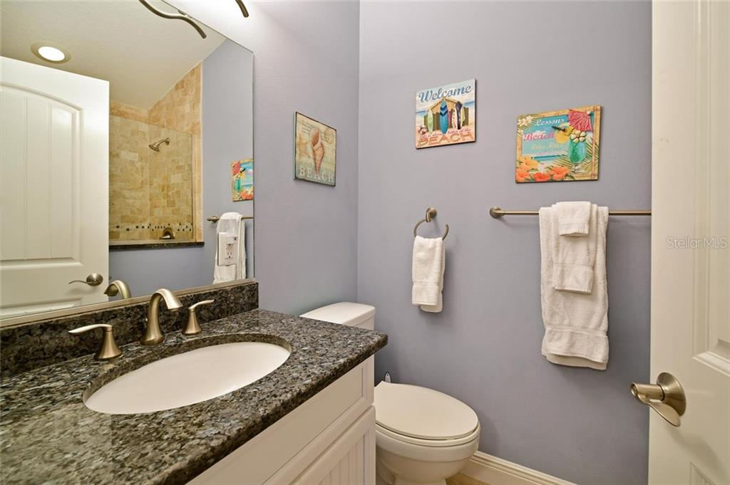 This bath with elegant glass shower (seen in mirror) complements the large second floor bedroom suite. - Single Family Home for sale at 113 36th St, Holmes Beach, FL 34217 - MLS Number is A4407267