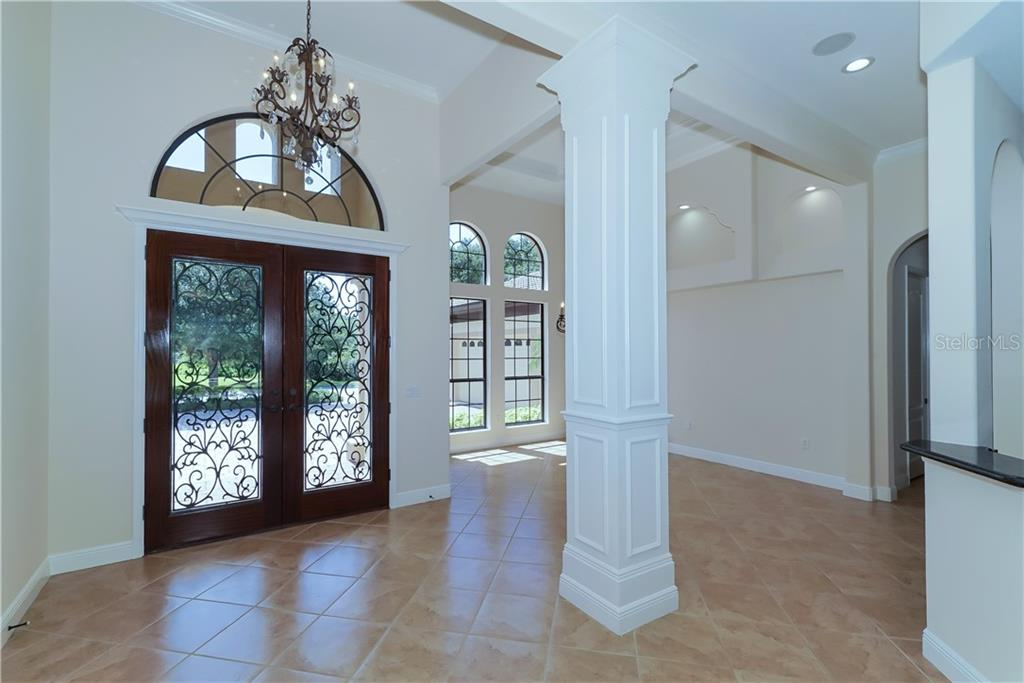 Front entry and formal dining room with crown molding, volume ceilings, exquisite architectural finishes and display niches. - Single Family Home for sale at 13219 Palmers Creek Ter, Lakewood Ranch, FL 34202 - MLS Number is A4407857