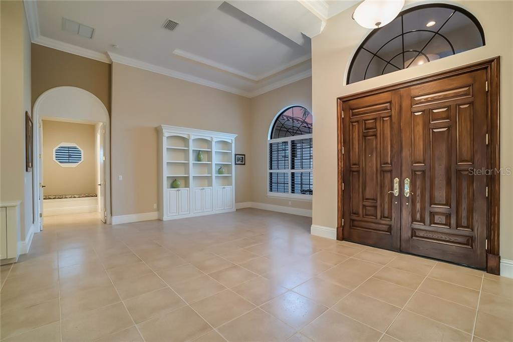 Custom front doors, bonus area with built-ins provide a variety of possible uses - reading, music, pool table?? The archway leads to the Owner's Master Suite. - Single Family Home for sale at 13223 Palmers Creek Ter, Lakewood Ranch, FL 34202 - MLS Number is A4408290