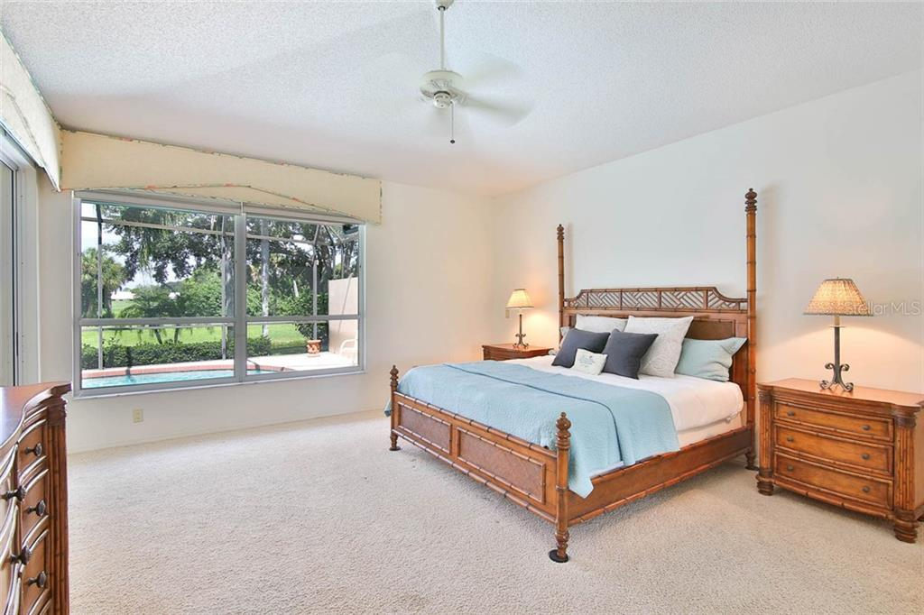 Spacious master bedroom with cathedral ceiling and beautiful views to the outside. - Villa for sale at 7686 Calle Facil, Sarasota, FL 34238 - MLS Number is A4413755