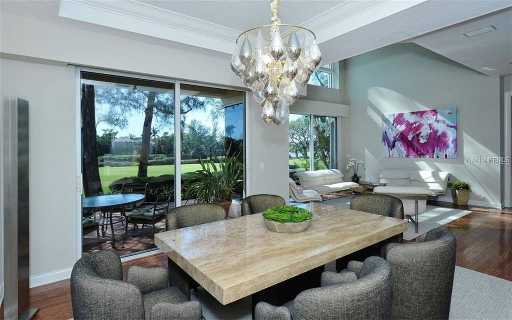 From the dining room you look into the living room and over the golf course. - Single Family Home for sale at 3529 Fair Oaks Ln, Longboat Key, FL 34228 - MLS Number is A4414992