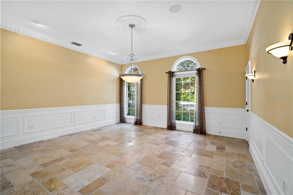 Spacious formal dining room, with intricate crown molding, scone and recessed lighting, wainscoting, floor to ceiling windows with transom and a walk-in closet with built-in shelves. - Single Family Home for sale at 1654 Landings Blvd, Sarasota, FL 34231 - MLS Number is A4417765