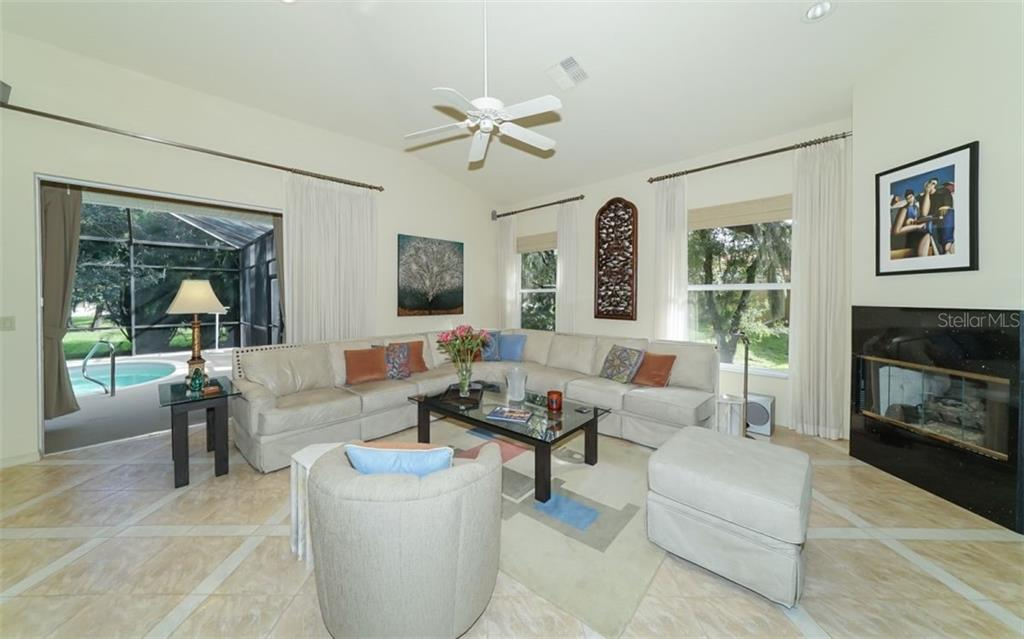 View from the kitchen into the large family room with gas fireplace. Pocket sliding doors lead to lanai & pool. - Single Family Home for sale at 6125 Varedo Ct, Sarasota, FL 34243 - MLS Number is A4420656