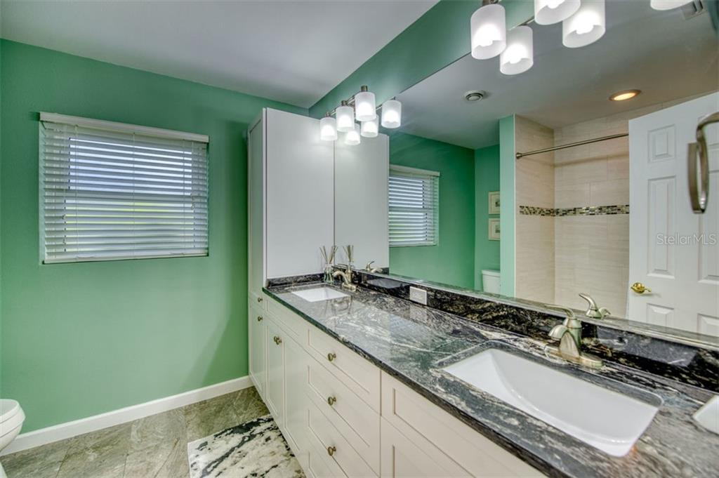 New guest bathroom with dual sinks - Single Family Home for sale at 5548 Shadow Lawn Dr, Sarasota, FL 34242 - MLS Number is A4423461