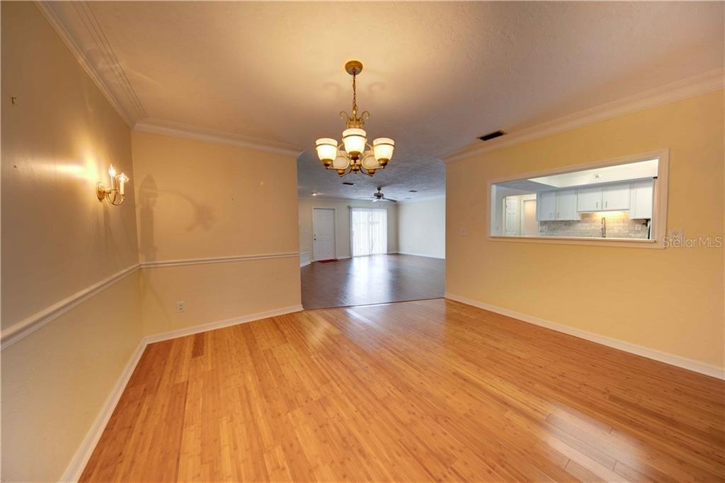 The large dining area looks through a pass through to the kitchen, into the great room and also the front room. You could use any size table here, large or small! - Single Family Home for sale at 6213 8th Avenue Dr W, Bradenton, FL 34209 - MLS Number is A4423560