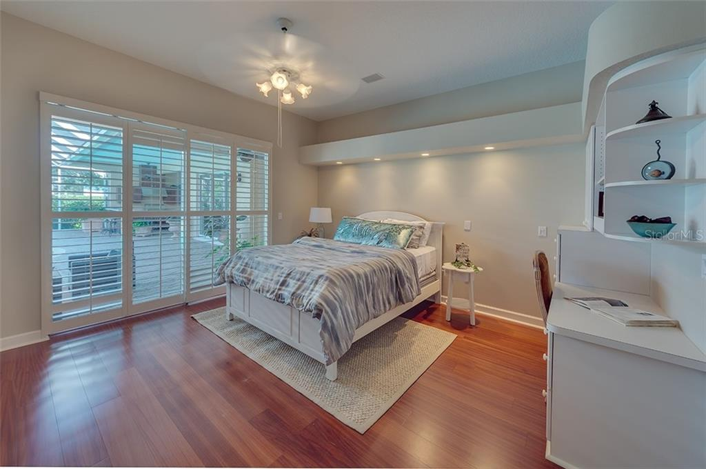 Ensuite guest bedroom with wood flooring. - Single Family Home for sale at 2972 Jeff Myers Cir, Sarasota, FL 34240 - MLS Number is A4424133