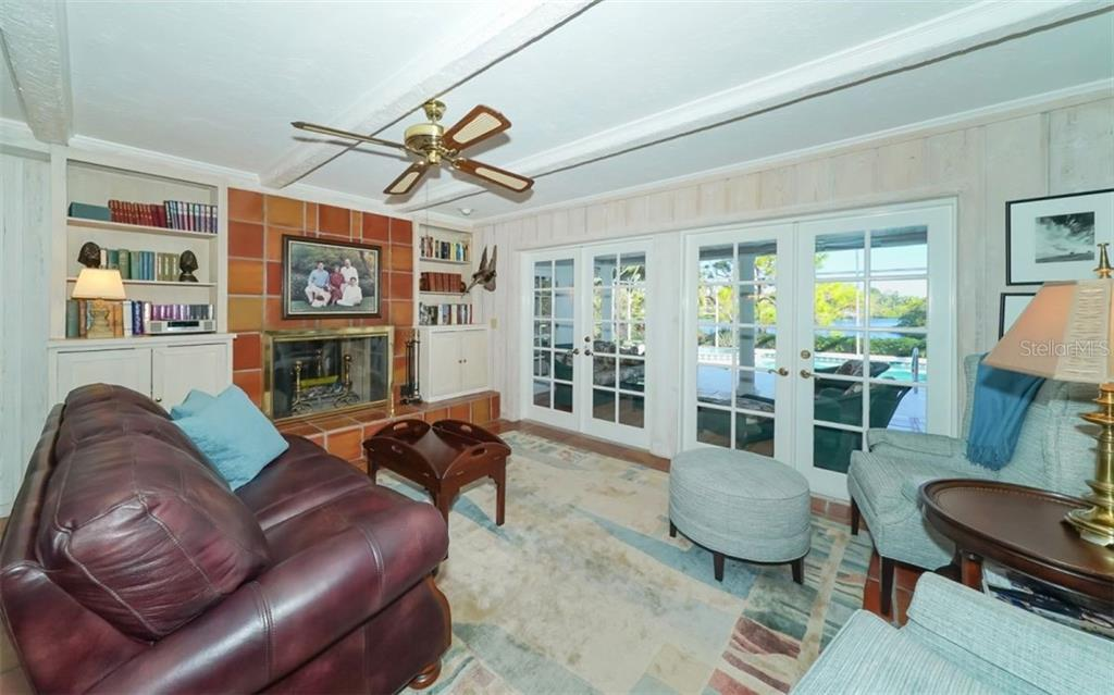 Family room with double French doors to the lanai and fireplace that opens on the other side to the games room - Single Family Home for sale at 510 63rd St Nw, Bradenton, FL 34209 - MLS Number is A4424601