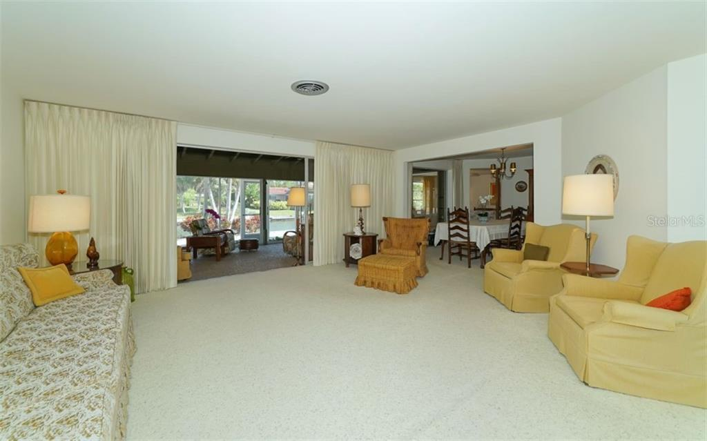 Spacious living room openng to the Florida room overlooking the canal. - Single Family Home for sale at 935 Contento St, Sarasota, FL 34242 - MLS Number is A4431223