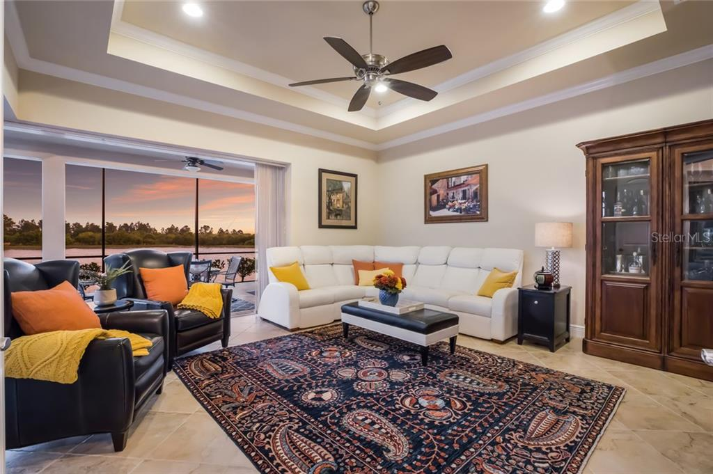 Family room with porcelain tile flooring and double tray ceiling with 180 degree lake views. - Single Family Home for sale at 19432 Newlane Pl, Bradenton, FL 34202 - MLS Number is A4432094