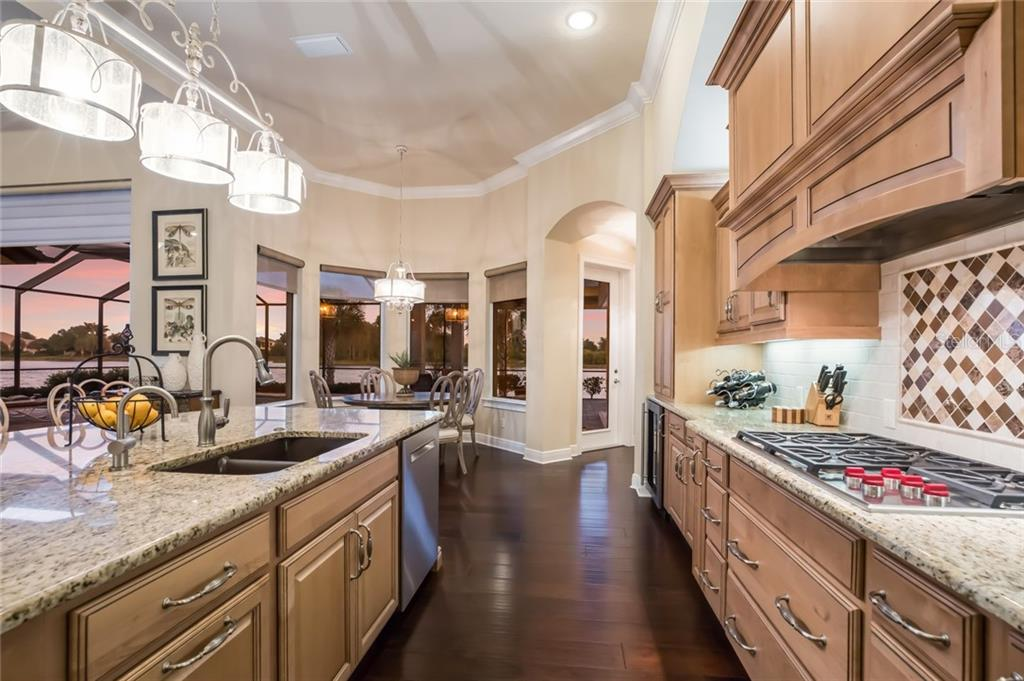 Among the large kitchen island the kitchen sink is comprised of crushed granite. - Single Family Home for sale at 19432 Newlane Pl, Bradenton, FL 34202 - MLS Number is A4432094