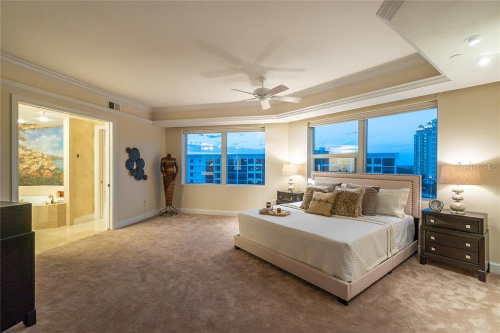 Evening ambiance in your Expansive Master Suite which includes a luxurious ensuite, walk-in closet with fabulous built-ins, seating area to relish the views and formal office. - Condo for sale at 128 Golden Gate Pt #902a, Sarasota, FL 34236 - MLS Number is A4433296