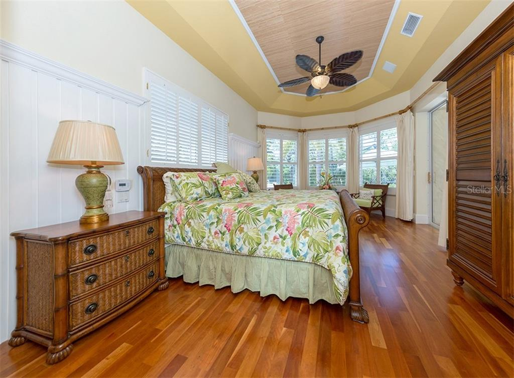 Master bedroom - Lauzon Next Step American Cherry wood flooring, Tray ceiling, custom milled lap cypress, Plantation Shutters and sliders leading to patio area - Single Family Home for sale at 1361 Bayshore Dr, Englewood, FL 34223 - MLS Number is A4433943