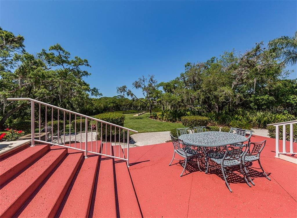 Patio to yard - tropical landscaping with boardwalk to boat dock & Forked Creek - Single Family Home for sale at 1361 Bayshore Dr, Englewood, FL 34223 - MLS Number is A4433943