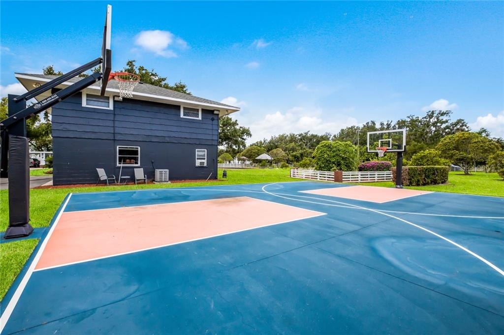 Basketball court next to the guesthouse, garden beyond. - Single Family Home for sale at 590 Bayshore Dr, Terra Ceia, FL 34250 - MLS Number is A4437024