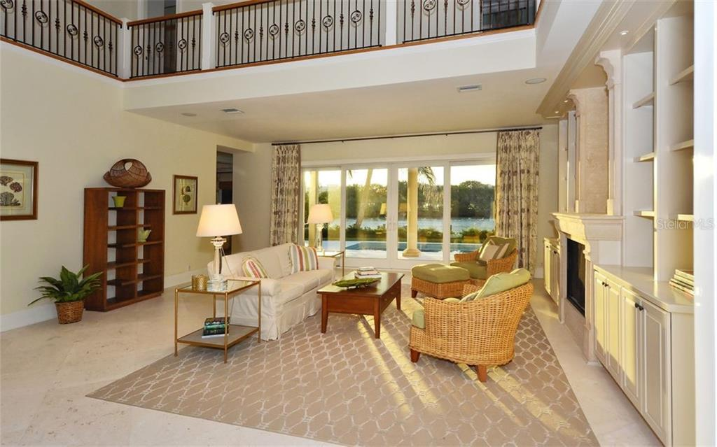 Living room with gas fireplace overlooking the pool terrace and lagoon - Single Family Home for sale at 65 Lighthouse Point Dr, Longboat Key, FL 34228 - MLS Number is A4438181