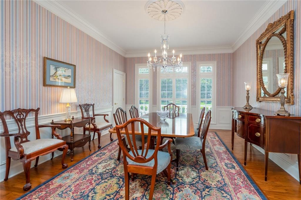 Formal dining room with large windows for natural light, a deep walk-in storage closet, beautiful chandelier with ceiling medallion, and intricate architectural moldings! - Single Family Home for sale at 3702 Beneva Oaks Blvd, Sarasota, FL 34238 - MLS Number is A4438878
